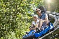 Der Mann und Mädchen, die eine Sommerspaßachterbahn genießen, reiten Lizenzfreie Stockbilder