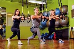 Der Mann und zwei Frauen, die trx Bügelübungen in einer Turnhalle tun, schlagen mit einer Keule Stockbild