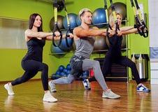 Der Mann und zwei Frauen, die trx Bügelübungen in einer Turnhalle tun, schlagen mit einer Keule Stockfotos