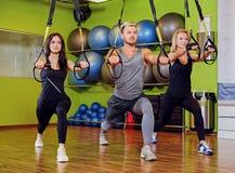 Der Mann und zwei Frauen, die trx Bügelübungen in einer Turnhalle tun, schlagen mit einer Keule Stockbilder