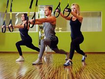 Der Mann und zwei Frauen, die trx Bügelübungen in einer Turnhalle tun, schlagen mit einer Keule Lizenzfreies Stockfoto