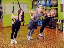 Der Mann und zwei Frauen, die trx Bügelübungen in einer Turnhalle tun, schlagen mit einer Keule Lizenzfreies Stockbild