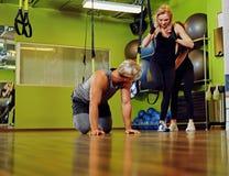 Der Mann und zwei Frauen, die trx Bügelübungen in einer Turnhalle tun, schlagen mit einer Keule Stockfoto