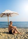 Der Mann unter einem Solarregenschirm Stockbild