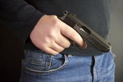 Der Mann versteckte das Gewehr hinter ihren Rückseiten, Raub, das Verbrechen und entführte lizenzfreies stockfoto