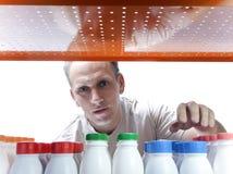Der Mann wählt Milchprodukte im System aus Lizenzfreies Stockfoto