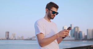 Der Mann w?hlt die Nummer am Telefon und spricht auf dem Hintergrund des Panoramas von Dubai Handnahaufnahme stock footage