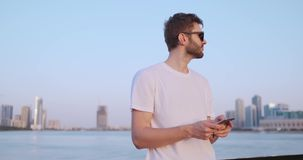 Der Mann w?hlt die Nummer am Telefon und spricht auf dem Hintergrund des Panoramas von Dubai Handnahaufnahme stock video footage