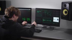 Der Mann, wie die Häcker ausgesehen, die versuchen, auf die Tastatur eines Computercodes hereinzukommen, um das Programm zu zerha stock footage