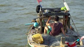 Der Mann wird sich zum Meer auf Fischen heraus setzen Der Mann schwimmt hinunter den Fluss im kleinen Fischerboot vietnam stock video footage