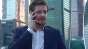 Der Mann wird von der Unterhaltung am Telefon erschrocken stock footage