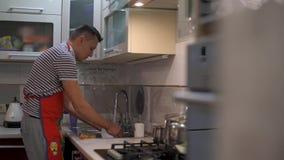 Der Mann wusch die Teller Schließen Sie oben von den Händen und vom Kran stock footage