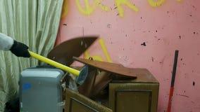 Der Mann zerstört ein altes Regal mit Tellern durch einen Vorschlaghammer stock video