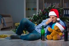 Der Mann, der zu Hause Weihnachten allein feiert Lizenzfreies Stockfoto