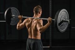 Der Mann, der zurück Hocken tut, trainieren mit einem Barbell stockfoto