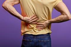 Der Mann, der zurück seins berührt, Kerl hat Scheibe peoblems in seiner Rückseite stockbilder
