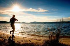 Der Mannathlet, der Zeit während des Trainings überprüft, lassen Übung draußen am Ozeanstrand am sonnigen kalten Morgen laufen Stockfotos
