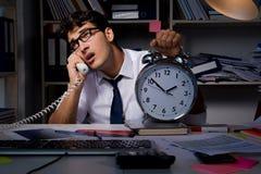 Der Manngeschäftsmann, der späte Stunden im Büro bearbeitet Stockfoto