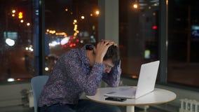 Der Mannmanager sitzt am Laptop und hält seinen Kopf erfahrungen Außerhalb des Fensters die Nachtstadt stock footage