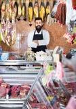 Der Mannverkäufer, der Fleisch gruppiert, um in den butcher's zu verkaufen, kaufen Stockbilder