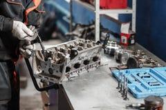 Der Mechaniker öffnete den Blockierungsventilmechanismus Bauen Sie Motorblockfahrzeug auseinander Bewegungskapitalreparatur Sechz stockfoto