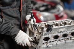 Der Mechaniker öffnete den Blockierungsventilmechanismus Bauen Sie Motorblockfahrzeug auseinander Bewegungskapitalreparatur Sechz stockbild
