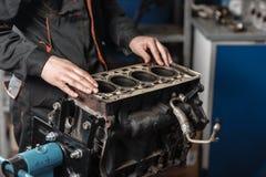Der Mechaniker bauen Blockmaschinenfahrzeug auseinander Maschine auf einem Reparaturstand mit Kolben und Pleuelstange von Automob lizenzfreie stockfotografie