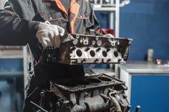 Der Mechaniker bauen Blockmaschinenfahrzeug auseinander Maschine auf einem Reparaturstand mit Kolben und Pleuelstange von Automob lizenzfreie stockbilder