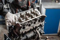 Der Mechaniker bauen Blockmaschinenfahrzeug auseinander Maschine auf einem Reparaturstand mit Kolben und Pleuelstange von Automob lizenzfreies stockbild