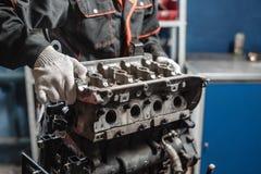 Der Mechaniker bauen Blockmaschinenfahrzeug auseinander Maschine auf einem Reparaturstand mit Kolben und Pleuelstange von Automob stockfotos