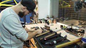 Der Mechaniker benutzt einen Hammer, um ein Fahrrad zu reparieren stock video footage