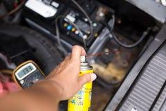 Der Mechaniker, der Aerosol hält, macht Sprayöl für Batterieersatz ein Lizenzfreie Stockbilder