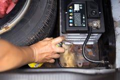 Der Mechaniker, der Aerosol hält, macht Sprayöl für Batterieersatz ein Stockbild