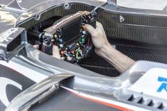 Der Mechaniker im Cockpit des Autos Hände auf dem Rad Lizenzfreie Stockfotografie