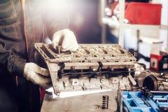 Der Mechaniker installiert ein neues Ventil Bauen Sie Motorblockfahrzeug auseinander Bewegungskapitalreparatur Sechzehn Ventile u stockbild
