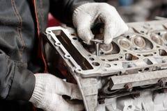 Der Mechaniker installiert ein neues Ventil Bauen Sie Motorblockfahrzeug auseinander Bewegungskapitalreparatur Sechzehn Ventile u lizenzfreie stockbilder