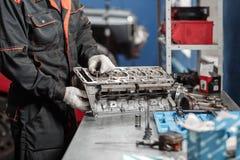 Der Mechaniker installiert ein neues Ventil Bauen Sie Motorblockfahrzeug auseinander Bewegungskapitalreparatur Sechzehn Ventile u stockfoto