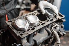 Der Mechaniker installiert einen neuen Kolben Bauen Sie Motorblockfahrzeug auseinander Bewegungskapitalreparatur Sechzehn Ventile stockfoto