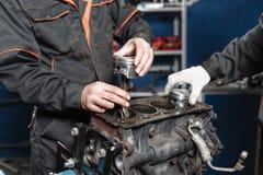 Der Mechaniker installiert einen neuen Kolben Bauen Sie Motorblockfahrzeug auseinander Bewegungskapitalreparatur Sechzehn Ventile stockbilder