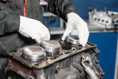 Der Mechaniker installiert einen neuen Kolben Bauen Sie Motorblockfahrzeug auseinander Bewegungskapitalreparatur Sechzehn Ventile stockfotografie