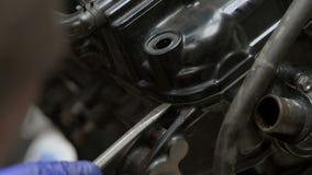 Der Mechaniker, der versucht, baut Motorradmaschine unter Verwendung des Schraubenziehers auseinander stock video footage
