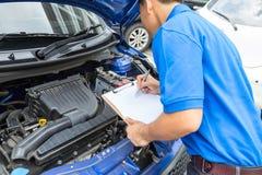 Der Mechanikermann, der Klemmbrett hält und überprüfen das Auto Stockbilder