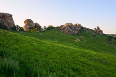 Der Megalithgranit auf dem Alpenwiesesonnenuntergang Stockfotografie