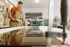 Der Meister arbeitet an einer Flachschleifmaschine lizenzfreie stockfotos