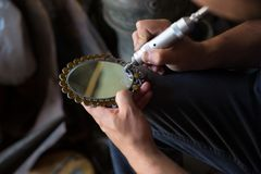 Der Meister das Spezialwerkzeug setzt Zeichnung auf einen Spiegel Stich auf Spiegel stockfotos