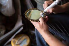 Der Meister das Spezialwerkzeug setzt Zeichnung auf einen Spiegel Stich auf Spiegel lizenzfreies stockfoto