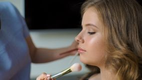 Der Meister in einem Make-up bildet den Studenten für Schluss aus Das Mädchen setzt eine Bürstengrundlage auf ein Gesicht des Kun stock video