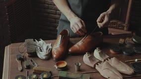 Der Meister fügt die Spitzee in die Schuhe ein stock video