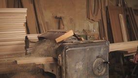 Der Meister im Overall fügt eine große Schiene in die Schleifmaschine, herauszieht sie ein Schreiner ` s Werkstatt stock video footage