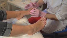 Der Meister interessiert sich für die Nägel und die Füße des Kunden und tut die Pediküre HD stock video